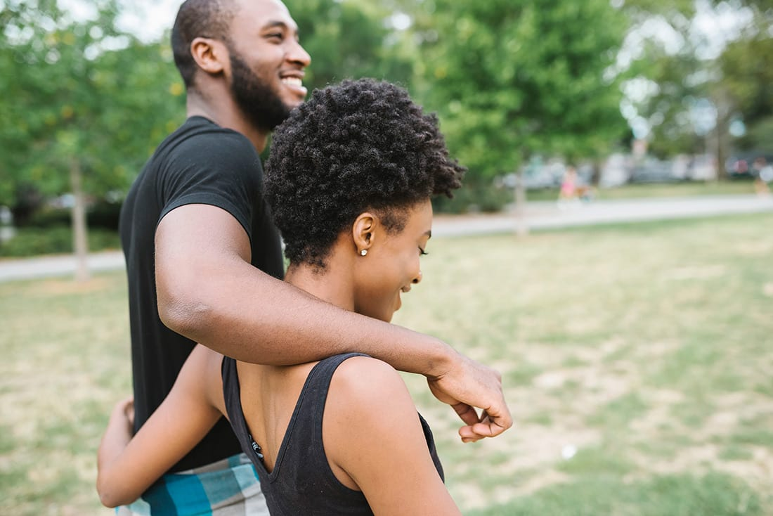 A couple walks through the park outside of Haller Post Apartments