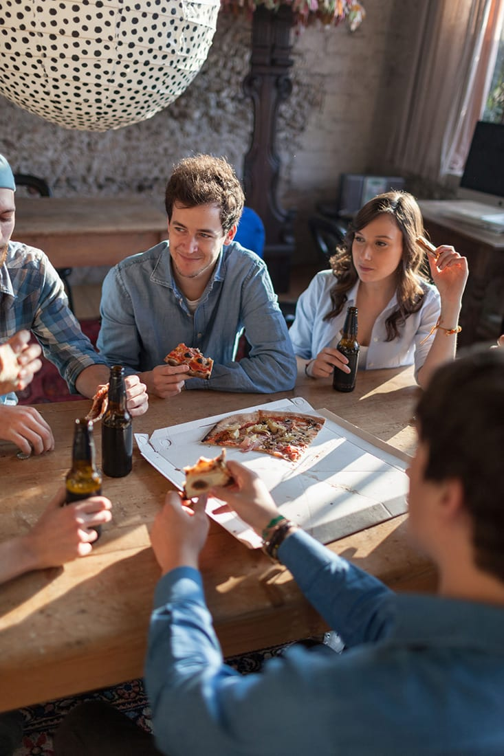 Friends enjoying pizza and beer