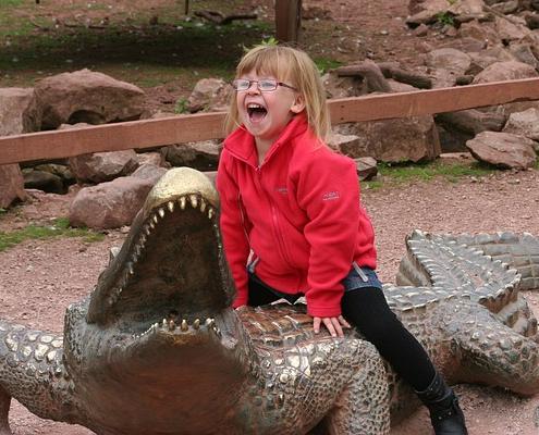 child riding crocodile statue at zoo