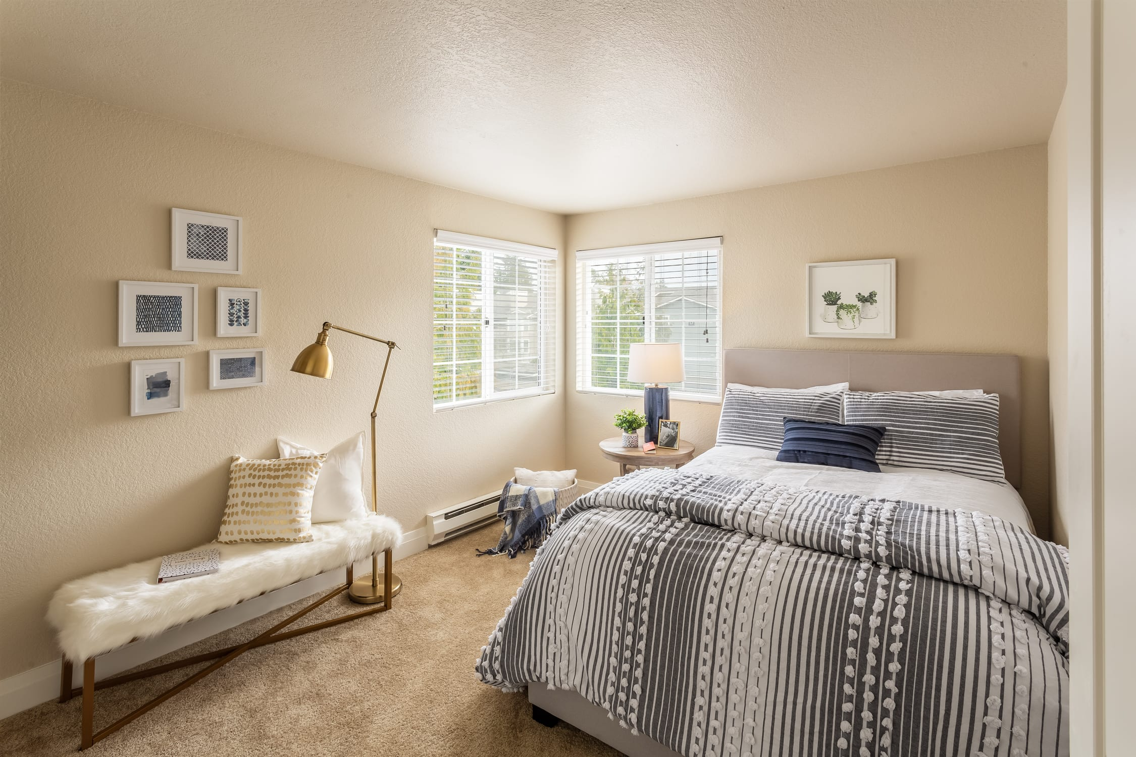 A bed, a small table, and a bench staged to show off a Haller Post Apartment bedroom