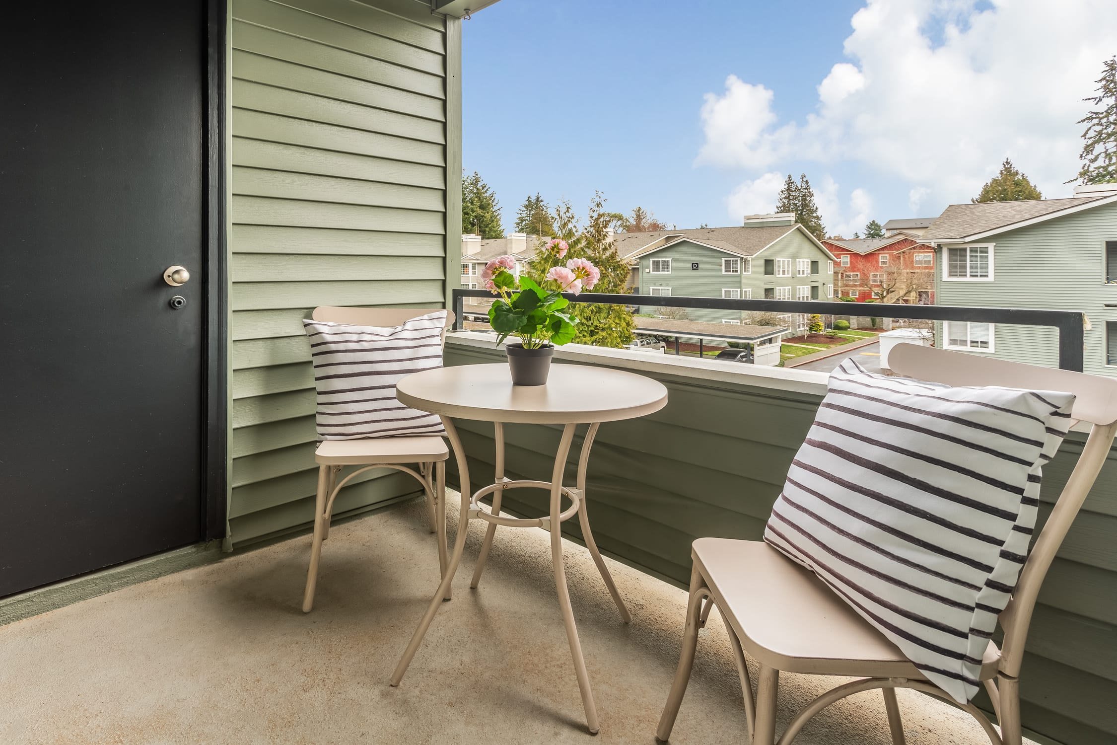 Two chairs with striped pillows, and a small table with a potted plant sit on the balcony at a Haller Post Apartment